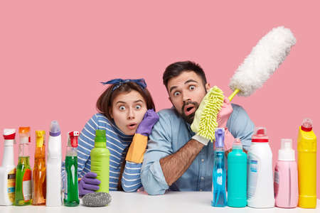 Photo of scared cleaning service workers stare at camera surprisingly, hold dust brush, bottle with chemical liquid, surprised to notice dirty room, isolated over pink studio wall. Omg and cleaning