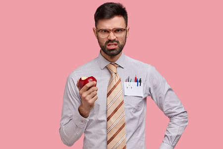 Discontent annoyed bearded man frowns face, clenches teeth with anger, eats juicy apple, doesnt like somebodys idea, dressed in formawear, irritated by interruption, models against pink background