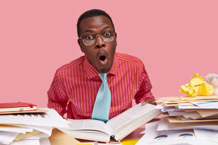 Comic horrified black male wonk holds thick opened book, stares in stupor, works on writing course paper, has pile of papers on table, dressed in formal shirt, isolated over pink background.