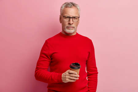 Indoor shot of handsome wrinkled man enjoys hot coffee from disposable cup, has work break, wears red jumper, poses over pink background, has serious stern look directly at camera. Pension concept