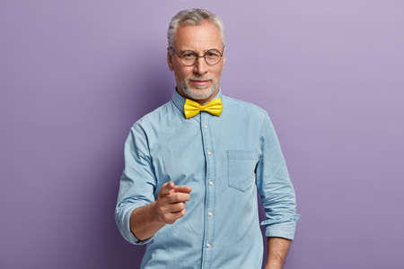 Join me, you wont regret. Handsome confident grey haired male professional fashion designer points at you, wears stylish shirt and yellow bowtie, chooses you, isolated over purple background