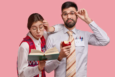 Attentive puzzled dark haired woman reads book, leans at shoulder of partner. Puzzled unshaven man holds rim of spectacles, eats delicious apple, poses over pink background. Reaction concept