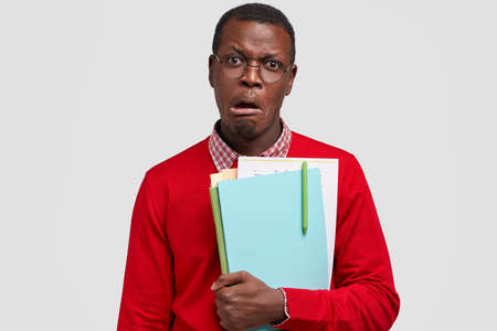 Discontent dark skinned man frowns face in dissatisfaction, carries papers, wears casual clothes, looks in displeasure, has no desire for studying, isolated over white background. People and dislike