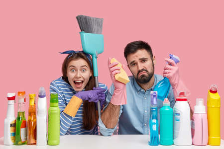 Cleaning concept. Sad young man holds cleanser and sponge, has unhappy expression, fed up with washing mirror, joyful lady points at guy, carries brush, work together, pose over pink studio wall