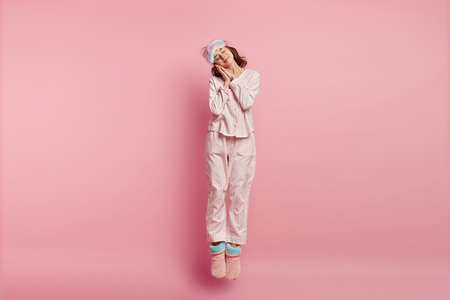 Positive restful lovely woman with eyes shut, enjoys sleeping at home, leans on hands, jumps in air, wears eyemask, nightclothes, domestic shoes, isolated over pink background. Bed time concept Stock fotó