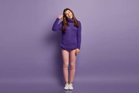 Positive young female foolishes indoor, imitates gun shoot, keeps hand near temple, tilts head and smiles broadly, wears purple loose sweater, trousers and sneakers. Full length shot. Body language