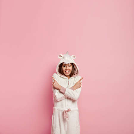 Vertical shot of positive woman with appealing look, crosses arms over chest, points at different sides, feels hesitation, cant understand what is right, wears warm kigurumi costume with hoody Stock Photo