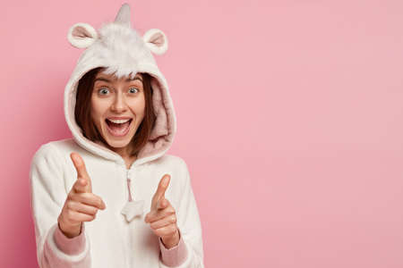 Isolated shot of happy European woman has pleased gaze at camera, points with both fore fingers directly at camera, wears casual domestic costume, isolated on pink wall, blank space for your text