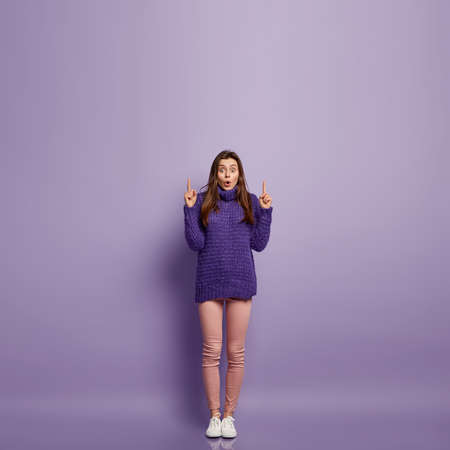 Photo of stupefied female model points above with both fore fingers, expresses wonderment, advertises product of high price, wears sweater and trousers, stands over purple background, empty space