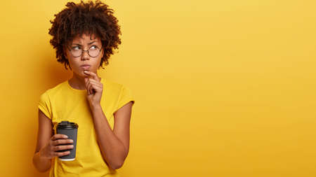 Studio shot of thoughtful African American woman holds chin, contemplates about something with angry serious expression, holds paper cup of hot drink, has coffee break, isolated on yellow wall