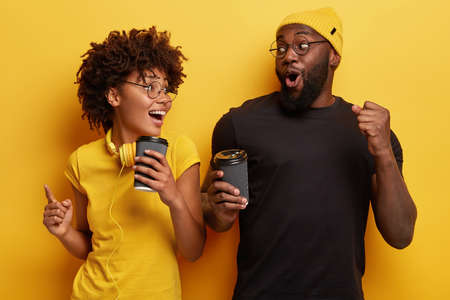 Happy joyful young woman and man look surprisingly positively, gesture actively while dance with loud music, drink takeaway coffee, celebrate successful day, isolated over yellow background. Фото со стока