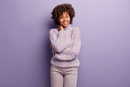 Indoor portrait of delighted cheerful dark skinned woman keeps hands behind neck, has tender smile, glad to receive compliment, expresses positive feelings, dressed in neat stylish purple outfit