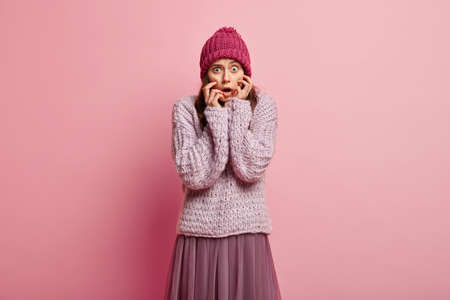 Omg concept. Scared pretty lady looks nervously at camera, afraids of something, wears warm hat, sweater and lush skirt, expresses fright, models over pink background. Emotions and feelings. Imagens