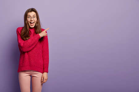 Horizontal shot of happy optimistic lady points aside at upper right corner, promots awesome thing, explains something emotionally, wears spectacles and red long sleeved sweater. Advert concept