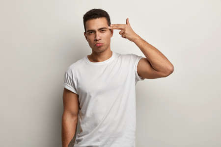 Horizontal shot of serious tired attractive guy shoots in temple with finger, demonstrates suicide gesture, wears white t shirt, fed up of long work, has strong body, isolated over white background.