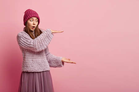 Shocked young European woman makes big gesture, keeps mouth widely opened, wears hat and knitted jumper, shows height of something, isolated over pink background. Thats enough big, I should say