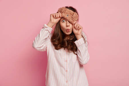 Indoor shot of surprised girl covers half of face with sleep mask, looks with shock, wears nightclothes, awakes after good sleep, amazed to notice something fearful, isolated over pink background