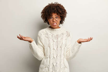 Unhappy dark skinned woman has displeased expression, spreads hands in bewilderment, can not find right decision, wears knitted sweater, clenches teeth with puzzlement, expresses uncertainty