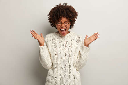 Unhappy desperate lady screams loudly, spreads palms, being full of negative emotions, feels irritated, wears white jumper, transparent glasses. African American curly woman yells with anger Stock Photo