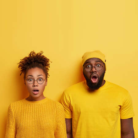 Omg, unbelievable. Stupefied Afro American companions hear shocking news or amazing plan from someone, have dark skin, stand against yellow studio wall with empty space above. Human facial expressions