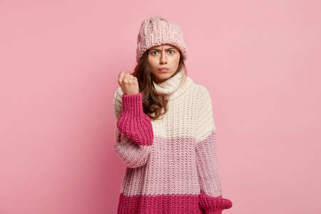 Photo of angry female model shows fist with irritated facial expression, demonstrates power, threatens to revenge, dressed in oversized jumper, has knitted hat, isolated over pink background.