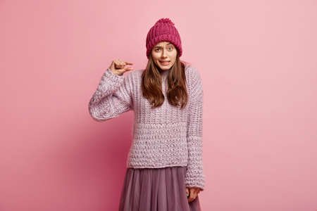 I need little bit. Puzzled lady shows very tiny object, shapes something small, wears headgear, knitted jumper and skirt, looks in puzzlement, isolated over pink background, gestures indoor.