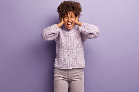 Emotional stressful woman keeps hands on ears, being under pressure, annoyed with irritated noise, screams loudly in panic, dressed in winter sweater, trousers, models against purple background Stock Photo