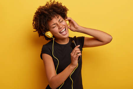 Carefree hipster with Afro haircut feels excited to hear new song, entertains herself with lively music, holds modern smart phone, sings while listens audio record, wears casual black t shirt
