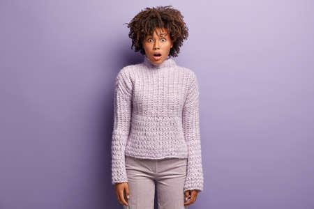 Studio shot of stunned pretty Afro American female entrepreneur surprised to fail, looks at camera surprisingly, has rush reaction, dressed in winter sweater, isolated over purple studio wall Фото со стока