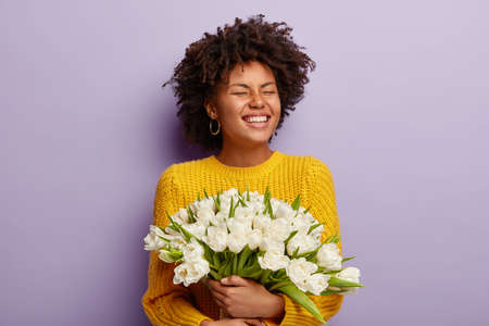 Satisfied dark skinned lady with overjoyed facial expression, closes eyes and shows white teeth, wears yellow clothes, likes flowers, holds white tulips, isolated over purple studio wall. Mothers Day