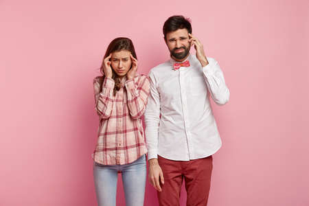 Indoor shot of frustrated thoughtful adult woman and man keep fingers on temples, try to concentrate on difficut question, stand closely, being deep in thoughts, isolated on pink background.