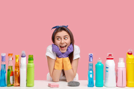 Glad female janitor keeps hands under chin, looks happily away, wears headband and casual t shirt, uses detergents and sponges for cleaning, isolated over pink background. Household concept. Stock fotó