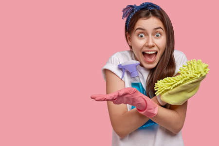Happy emotional woman crosses hands, holds mop and spray cleanser, wears white t shirt and gloves, glad to finish housework in time, not late for date, poses against pink wall. Good mood for cleaning