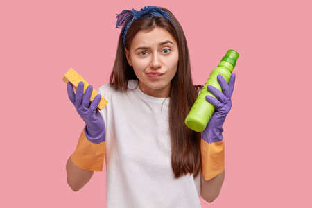 Housekeeping and cleaning concept. Unhappy confused young female janitor with long hair, holds sponge and green bottle with detergent, wears rubber gloves for hand protection, does house chores