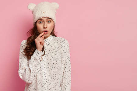 Photo of worried beautiful woman with intriguing expression, keeps hand near slightly opened mouth, hears rumors with interest, wears white headgear and polka dot shirt, stands over pink wall