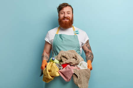 Everyday routine and housework concept. Shot of glad ginger man holds basin with clean washed laundry, being in good mood, dressed in casual clothes, has tattoos on arms, isolated on blue wall Standard-Bild