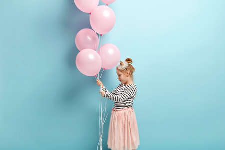 Sideways shot of ginger small child in striped top and tulle skirt, enjoys sweet moments of happy childhood, celebrates Childrens Day, holds many air balloons, stands against blue background