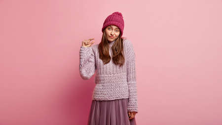 Unimpressed attractive young woman shows something tiny, demonstates little sign, wears pink headgear and winter sweater, makes hand gesture, offers to drink small amount of coffee. Size concept