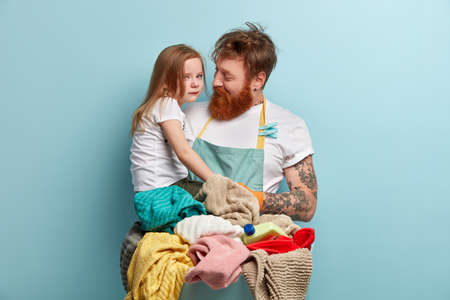 Redhaired single father busy with housekeeping, tires to calm little daughter who cries, pays attention and upbrings child, washes laundry, dressed in casual clothes. Fatherhood and business concept
