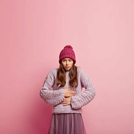 Dissatisfied young woman suffers from period cramps, has stomachache, keeps hands on belly, wears hat, loose sweater and skirt, models over pink background with blank space for your promotion