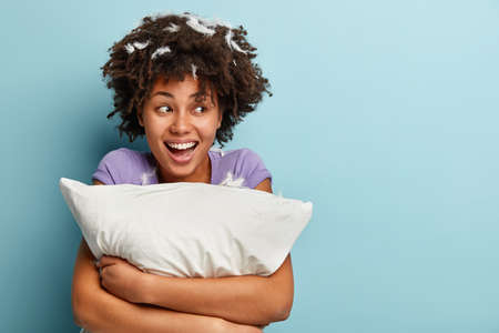 Photo of optimistic dark skinned woman with curly hair, embraces soft pillow, has good mood after afternoon slumber, poses with feathers on head, poses over blue wall, blank space for information