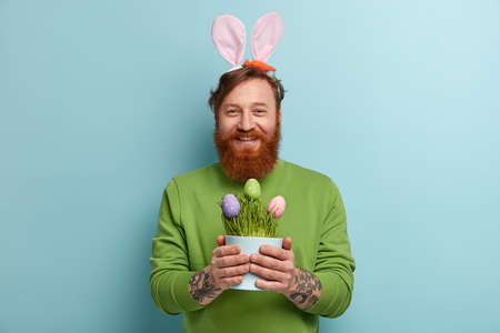 Positive red haired man with thick bristle, being cheerful funny Easter bunny who carries colored eggs, has rabbits ears, dressed in green jumper, prepares for important holiday. Happy moments