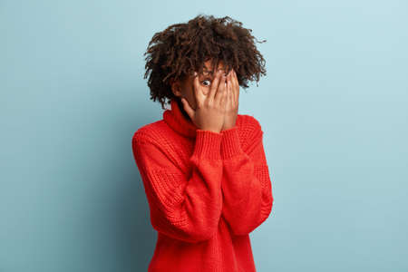 Indoor shot of young lady with Afro hair covers face with hands, peeks through fingers, hides from someone, has surprised expression wears red clothing afraids of something near. Oh no, take this away 免版税图像