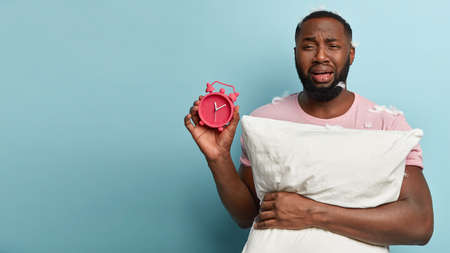 Sorrowful displeased black man carries red clock, sad being behind time, feels stress, fatigue of being early riser, overslept again, cries from despair, holds pillow, has dark skin, stands indoor