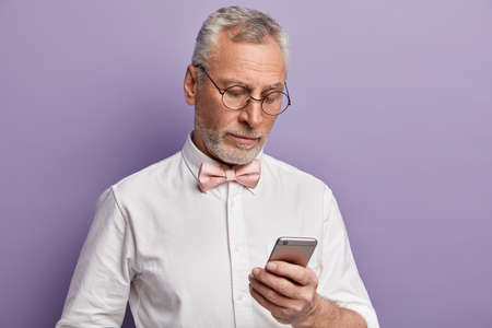 Senior man with grey hair and beard, dressed in formal clothes, focused at screen of cell phone, answers on received email, browses internet, transfers money via application connected to free internet