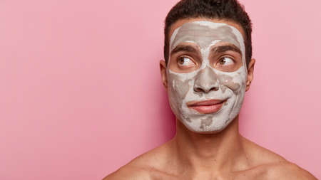 Skin care and peeling concept. Attentive man focused away, has white clay mask, uses beauty products and cosmetics, models over pink background with black space, being model for cosmetologist