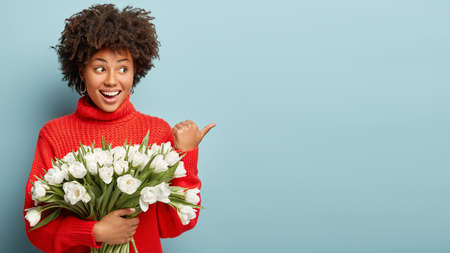 Portrait of satisfied dark skinned woman points away on her beloved man, says I recieved these beautiful flowers from him, wears red sweater, enjoys scent of tulips, smiles positively, advertises