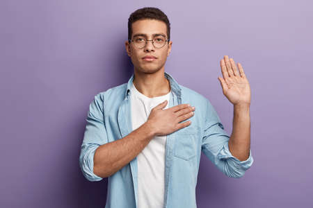 Honest serious hipster guy swears to do something, keeps hand on chest, gestures with palm, promises something, wears spectacles and denim shirt, swears indoor, isolated over purple background