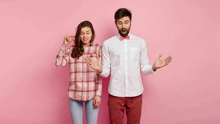 Studio shot of scared terrific bearded young man shapes very big object with both hands, puzzled woman demonstrates very little thing. Woman and man show size gesture, pose over pink background.