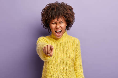 Annoyed pretty woman with curly hair accuses you, points straight at camera, being mad, blames her failures, shouts loudly from anger, isolated over purple background. You are guilty in my fault